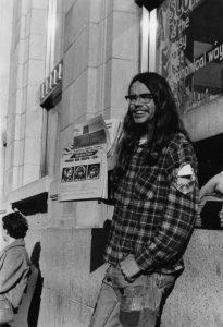 "Rick ""Lou Lemming"" James selling the radical rag Georgia Straight, corner of Yates and Douglas, Victoria, B.C., circa 1969"